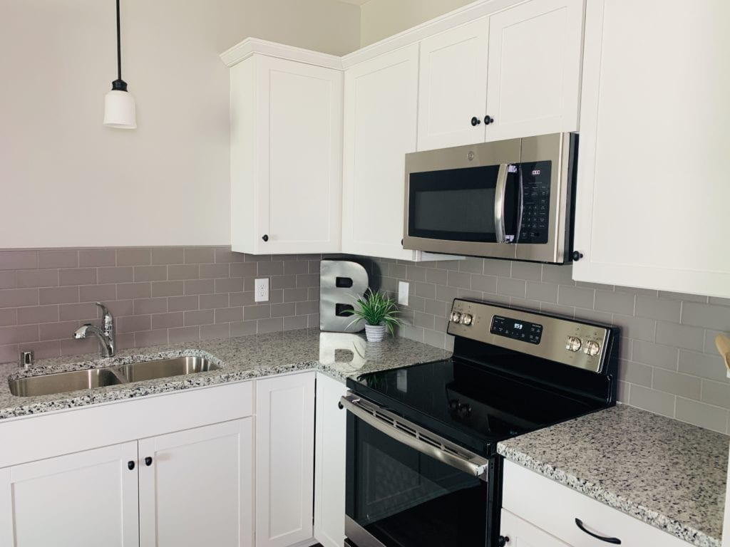 Modern kitchen with white cabinets, contrastic black and gray granite countertops and gray backsplash