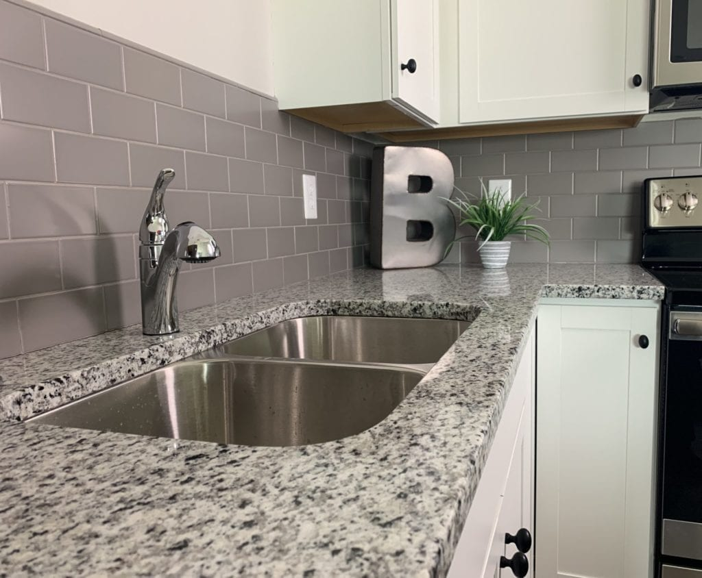Kitchen with granite countertops and white cabinets, and gray backsplash