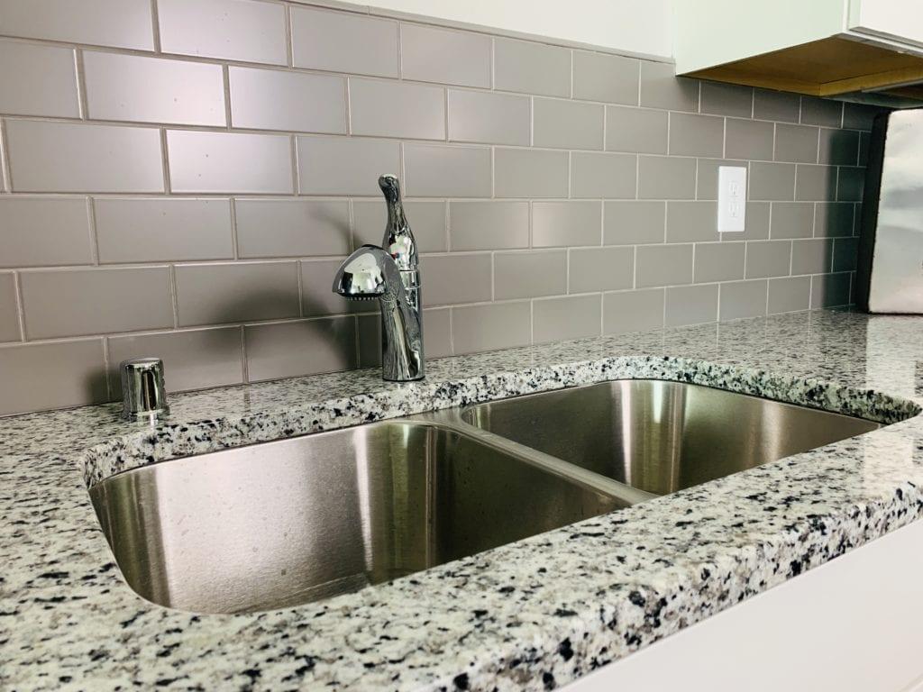 Kitchen granite countertops with gray tile backsplash