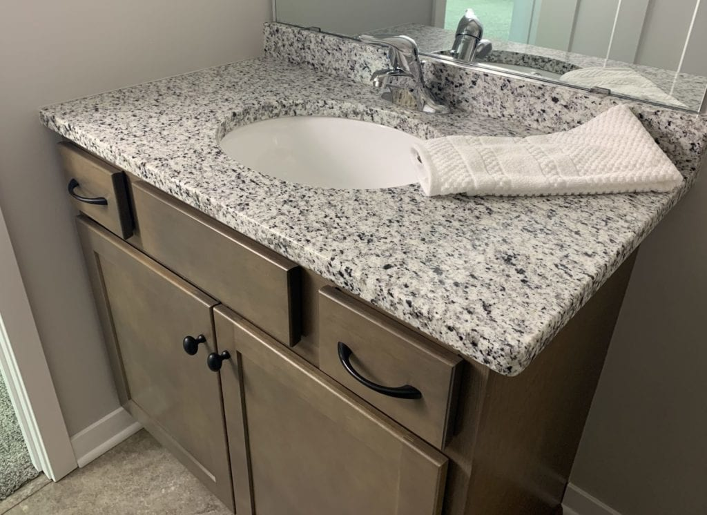 Bathroom vanity with granite countertop and brown cabinetry
