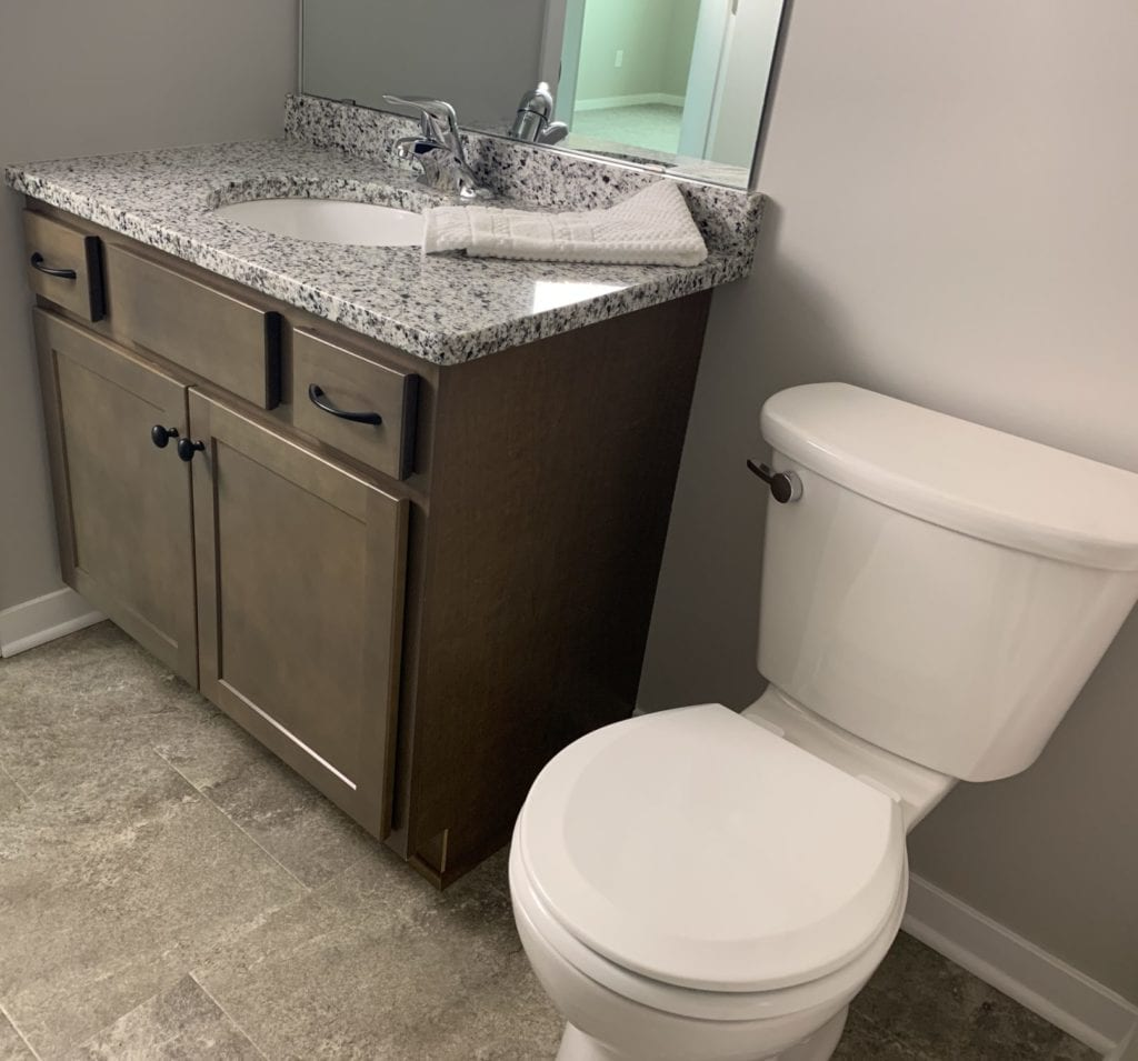 Bathroom with granite countertops and tile floors