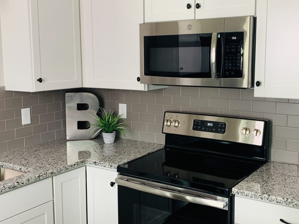 Modern kitchen with white cabinetry, gray tile backsplash and granite countertops