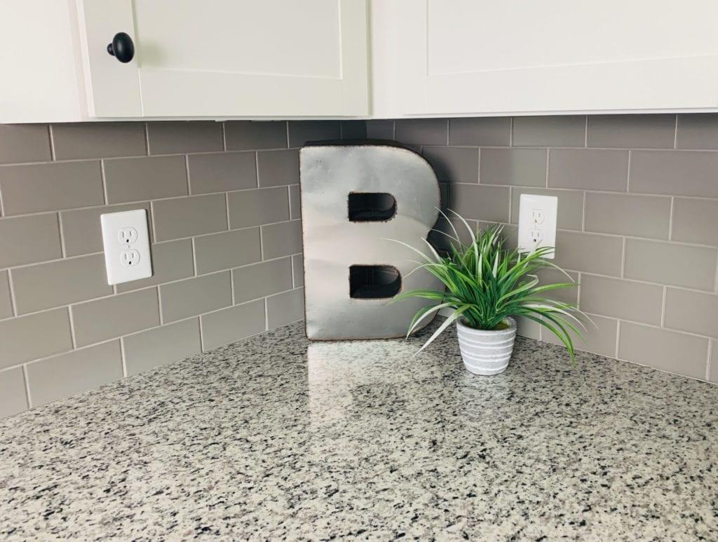 Gray tile backsplash with granite countertops