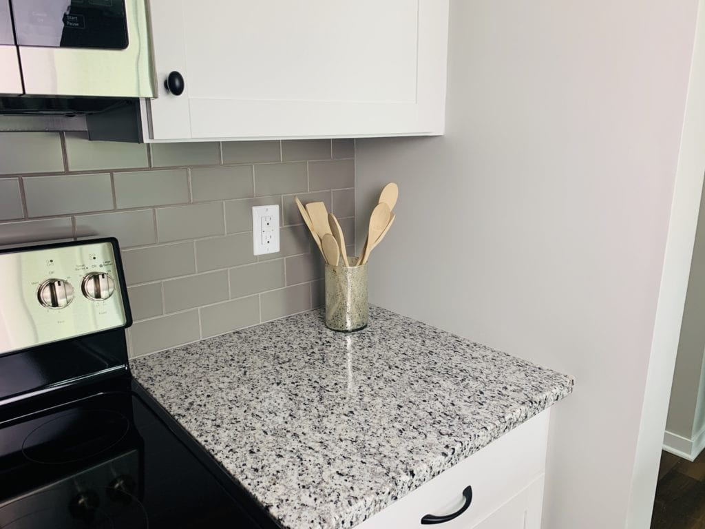 Gray tile kitchen basksplash with granite countertops and white cabinets