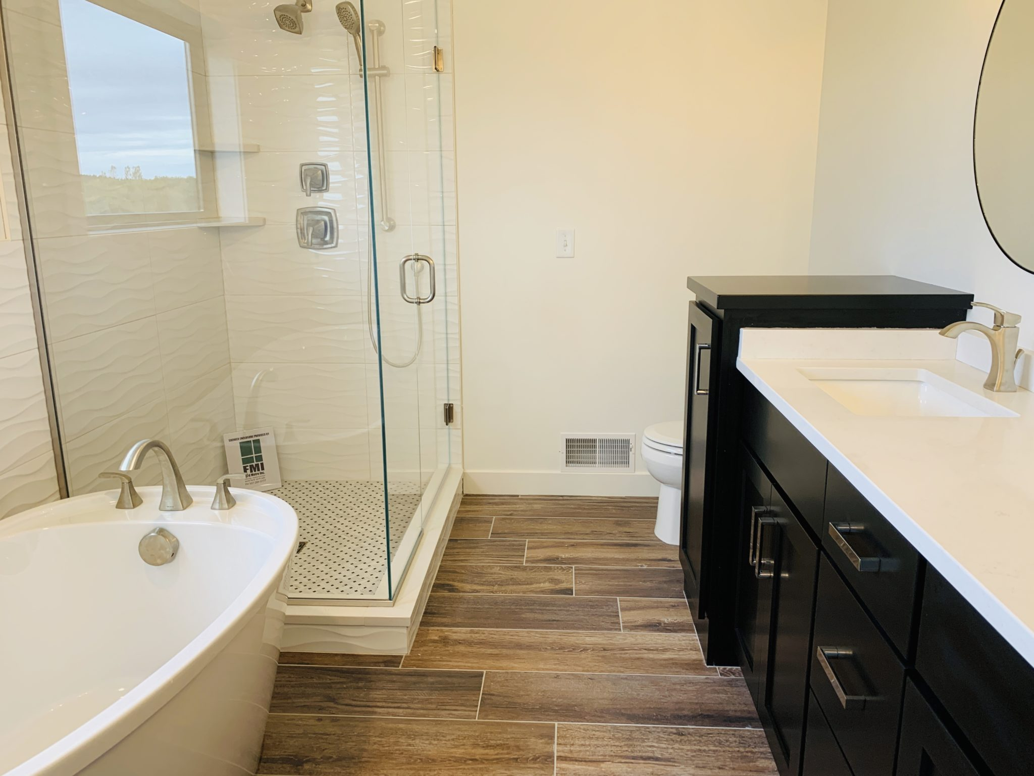 Bathroom with Luxury Vinyl Plank flooring and White Tile Shower