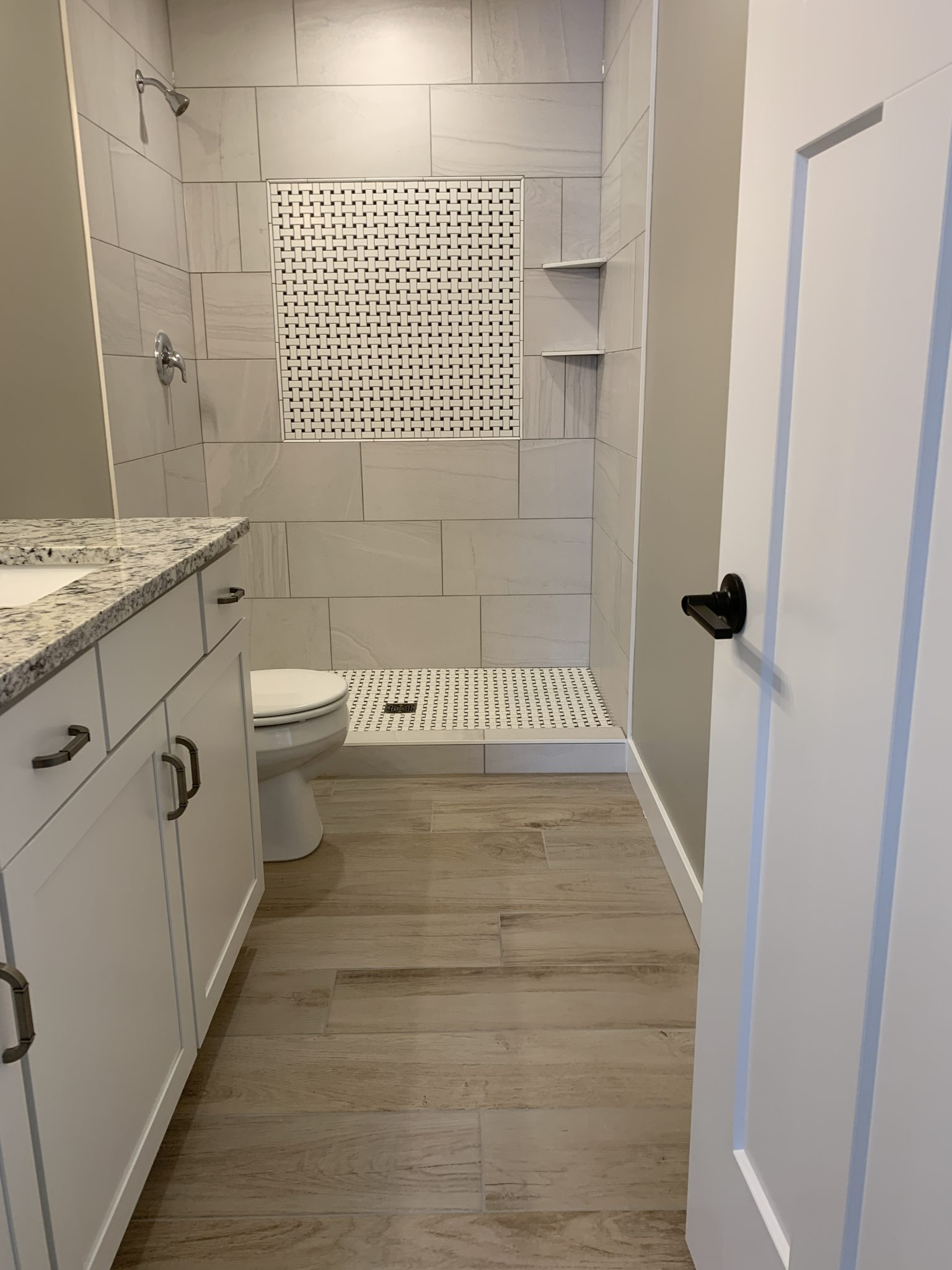 Bathroom with Luxury Vinyl Plank flooring, tile shower and white cabinets
